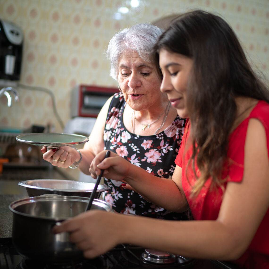 Mom and daughter cooking at stove