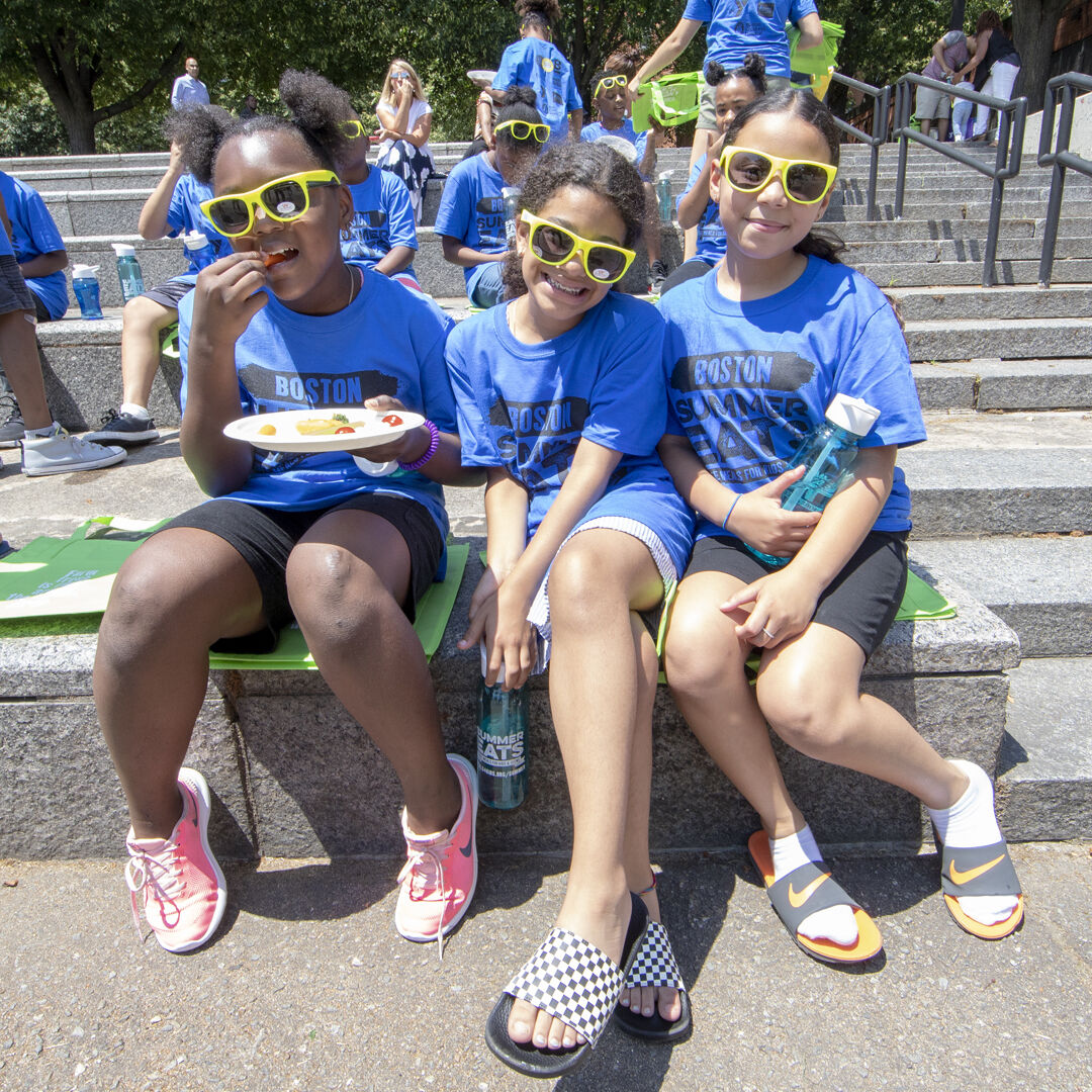 Three girls wearing sunglasses sitting next to each other, eating lunch through Boston Summer Eats