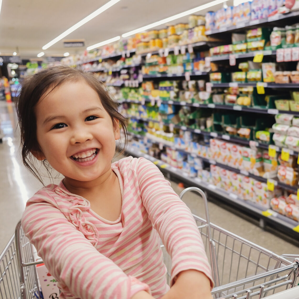 Happy little multiethnic girl sitting in a trolley, shopping cart at supermarket, grocery store
