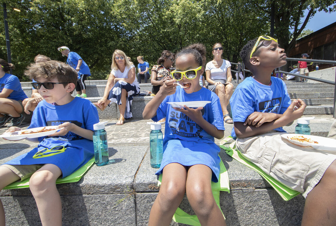 Three children sitting on edge of lawn with feet dangling, eating lunch at Boston Summer Eats site