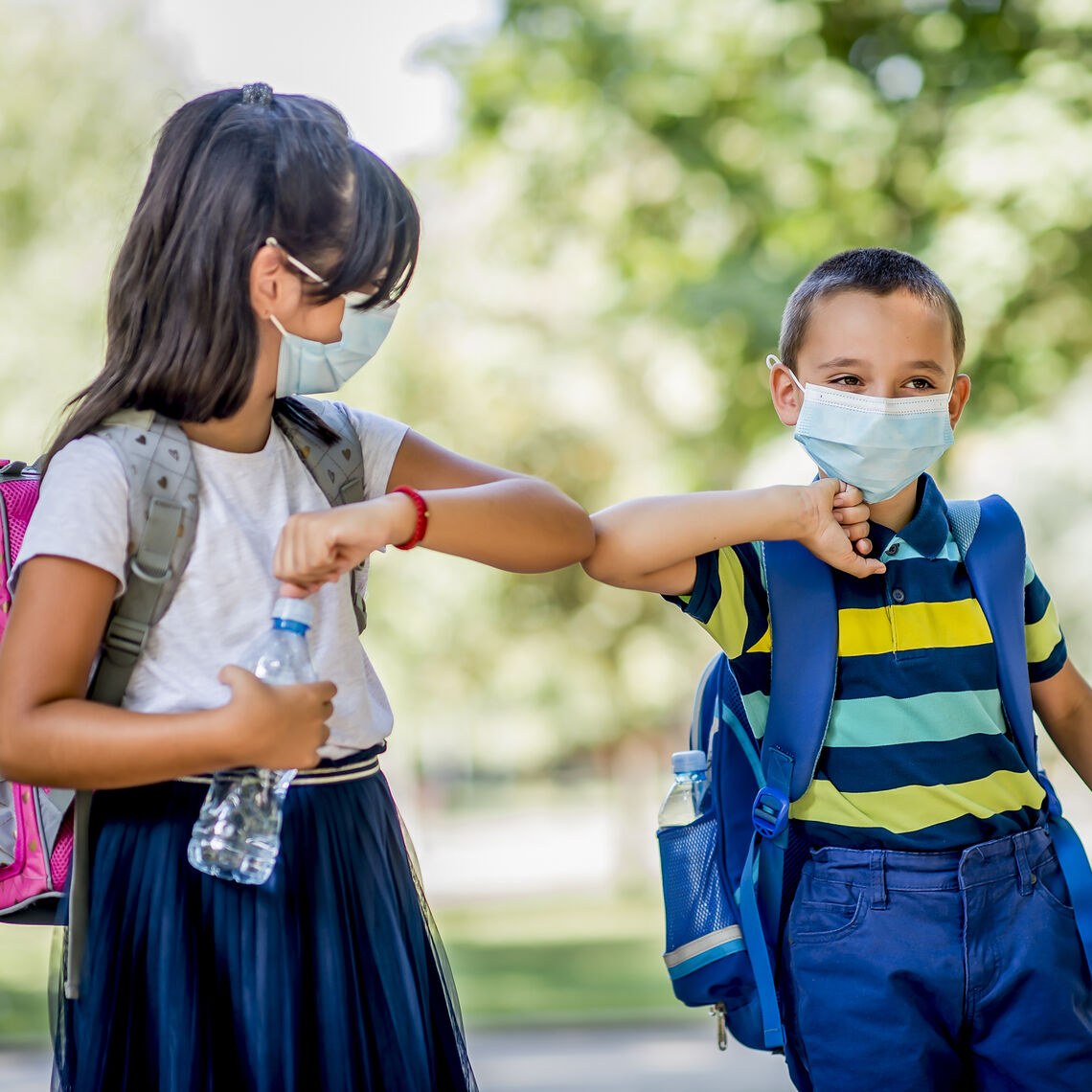 A young boy and girl wearing masks, bumping elbows outside with backpacks on