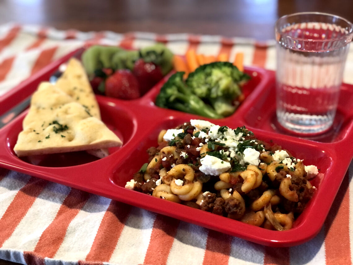 A red school lunch tray with Project Bread school lunch recipe, Amy Greek's Chop Suey served with pita, broccoli, and a fresh side of fruit