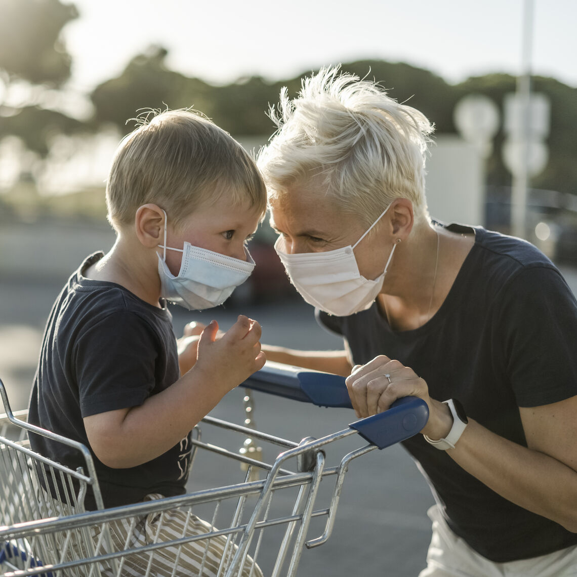 Mother joyfully playing with kid sitting in shopping cart. Both wearing protective face mask before entering a supermarket.