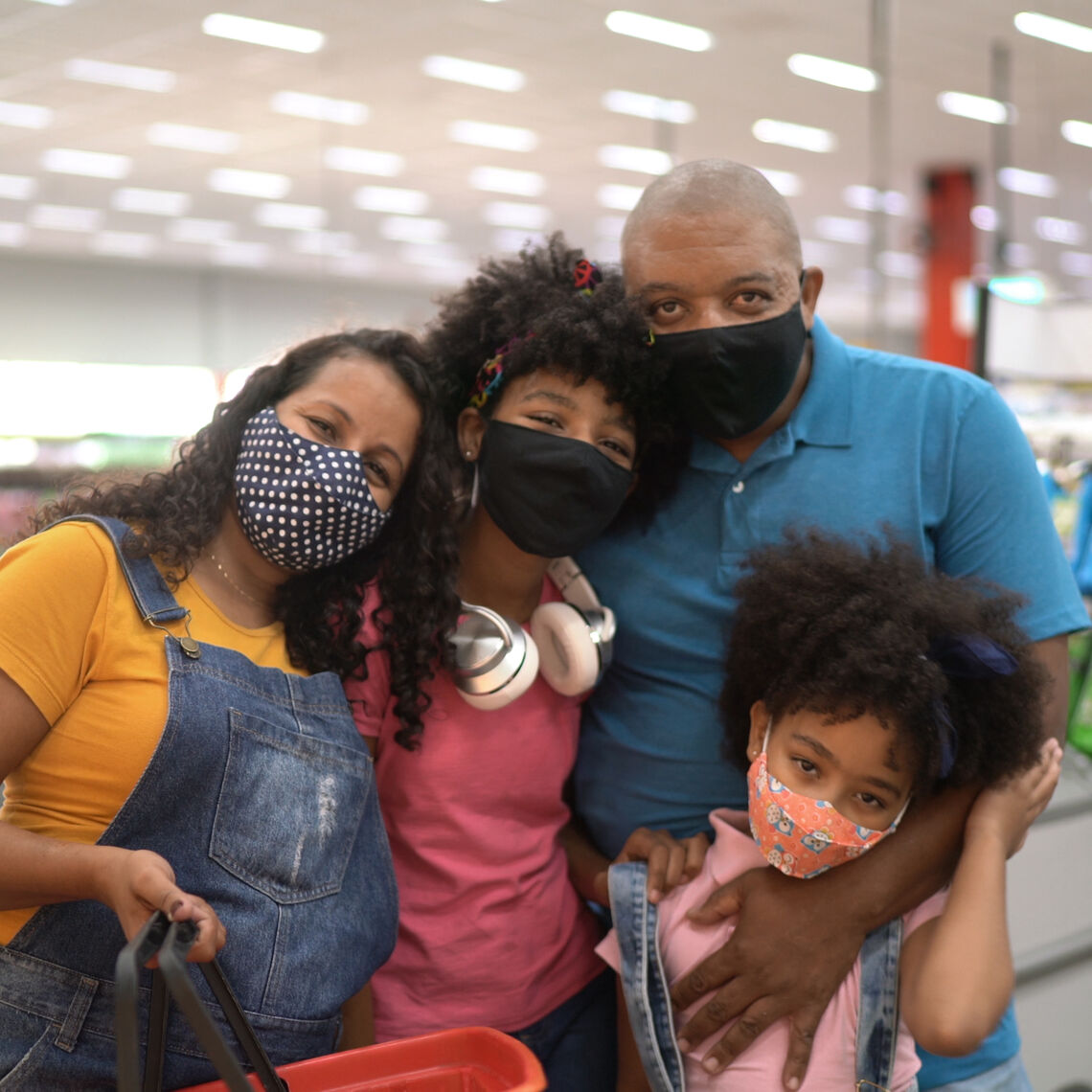 Family with two kids posing for a photo in the grocery store, with masks on