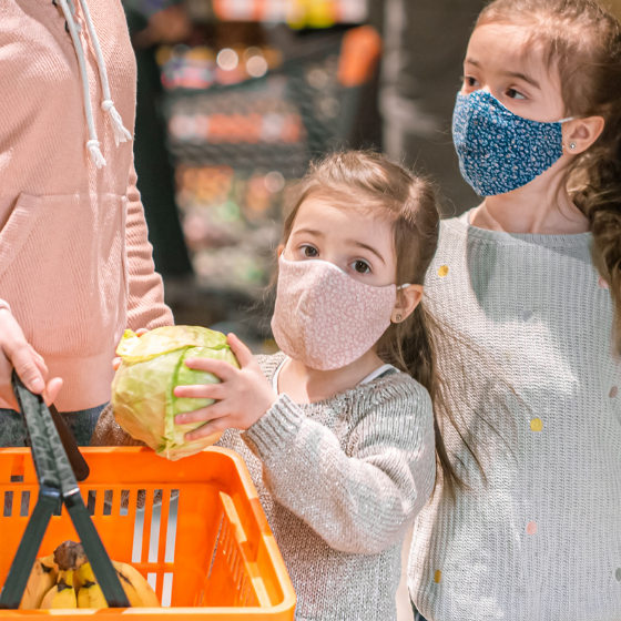 Two sisters with face masks help mom grocery shopping, adding a fresh head of lettuce to the basket