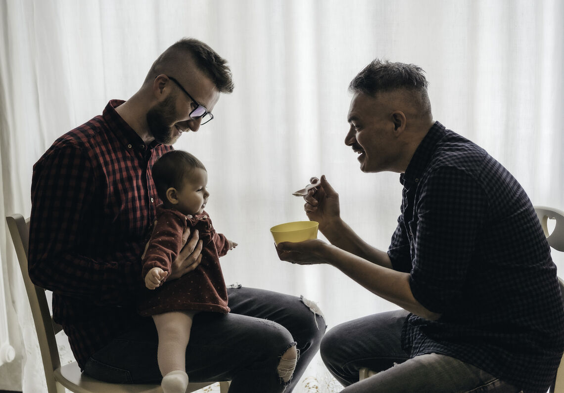 Two dads feed their baby girl in the kitchen