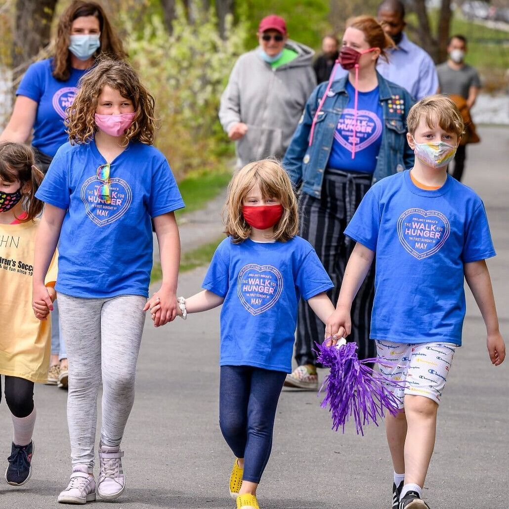 Children in Walk for Hunger t-shirts hold hands as they walk in front of adults.