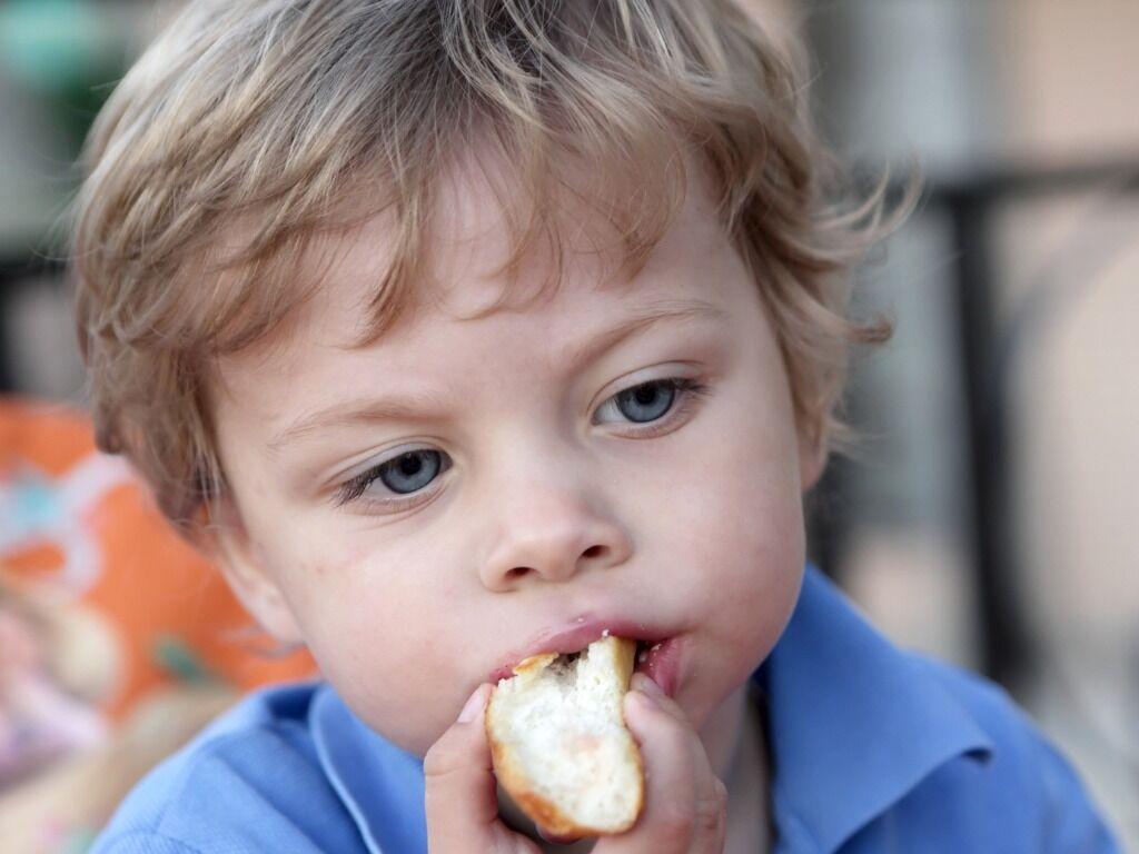 Little boy eating a piece of bread.