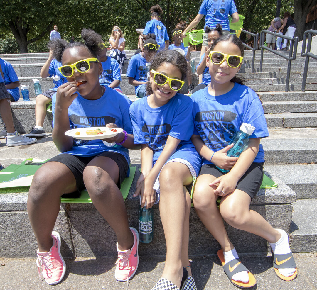 Three girls enjoy lunch at a Summer Eats meal site in Boston.