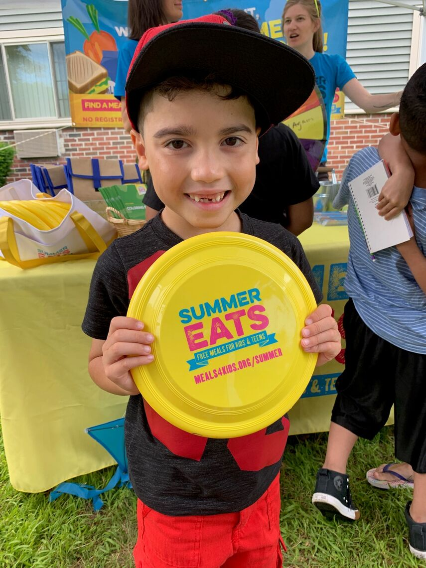 Little boy holds a frisbee with the Summer Eats logo.
