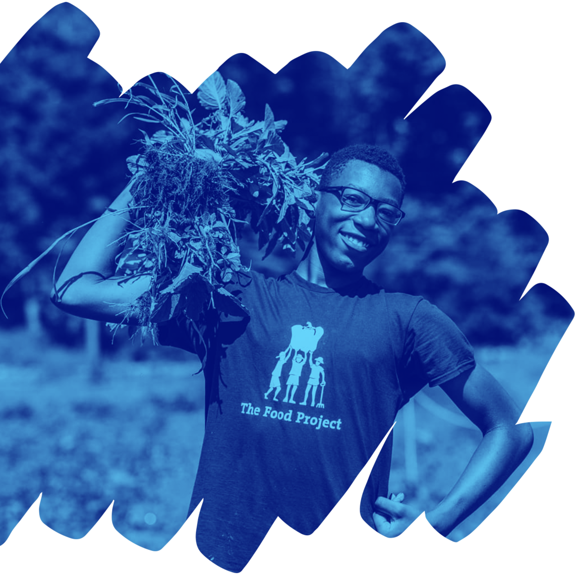 Image of a person with glasses holding harvested greens over their shoulder. Their other arm is bent with the hand making a fist against their hip. They are standing in a garden and smiling towards the camera.