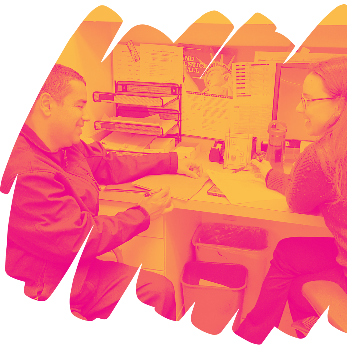 Two people sitting at a desk with papers and a computer on it. They are looking down at a piece of paper, one of them holding a pen.