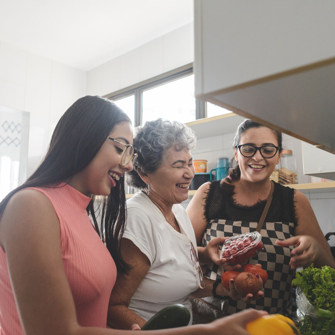Three generations of Latina women cooking in the kitchen together