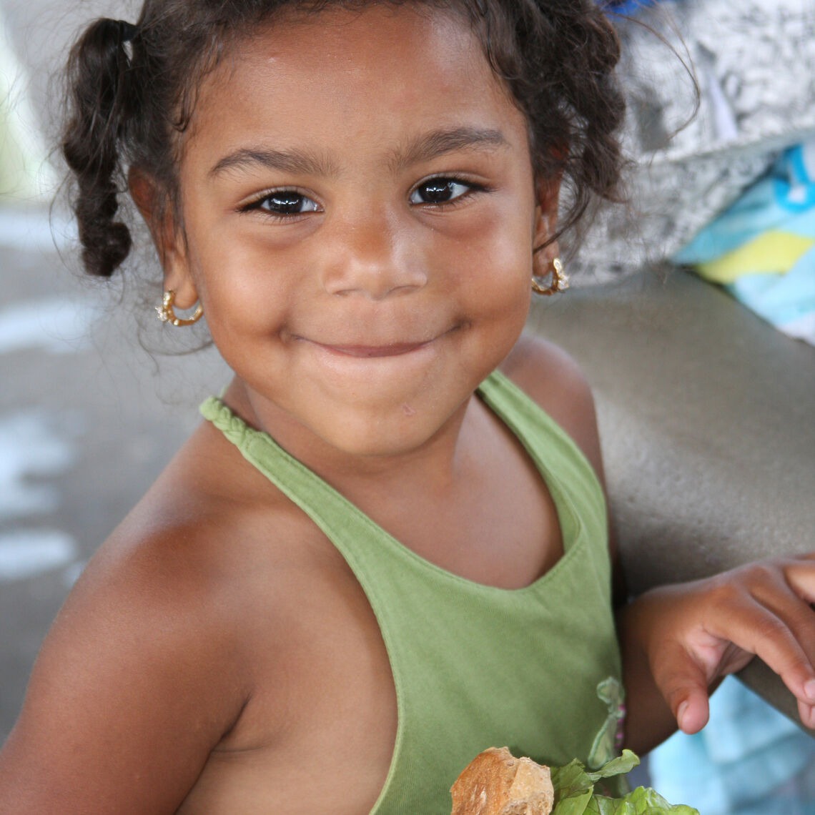 young girl eating a sandwich outside in the summer smiling