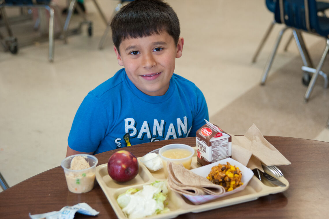 Young Latino boy smiling at school cafeteria table with a tray of black bean burrito lunch