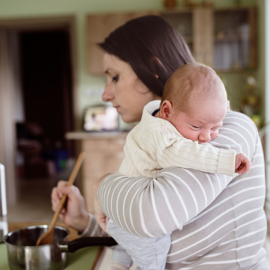 Beautiful young mother at home in the kitchen holding her newborn baby son, cooking, mixing something in pan (Beautiful young mother at home in the kitchen holding her newborn baby son, cooking, mixing something in pan.