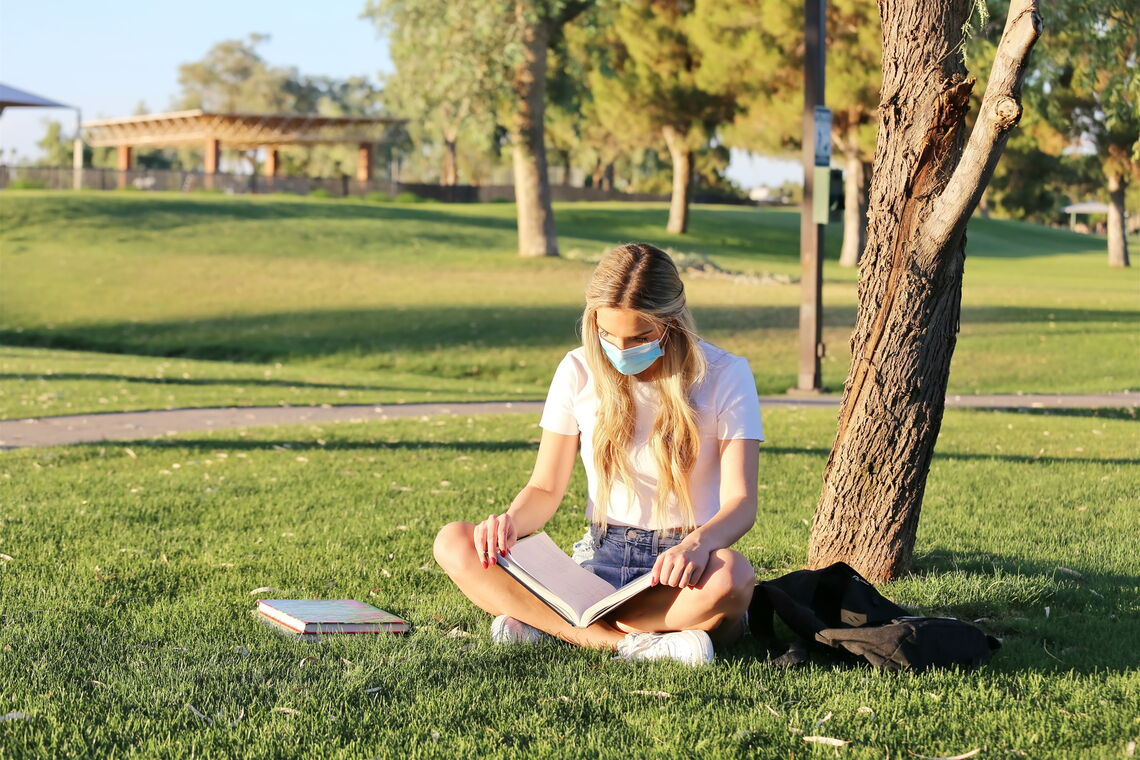 College student sits reading outside.
