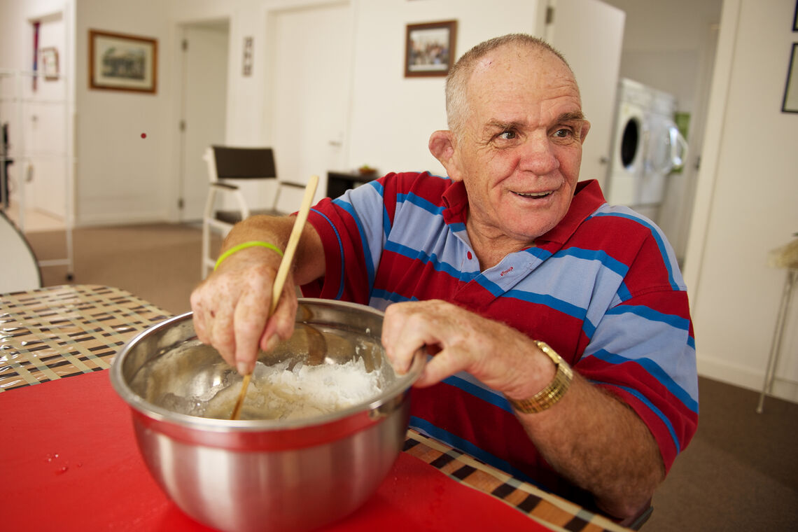 Senior disabled man stirs a bowl while he looks over his shoulder to see if he is doing it right