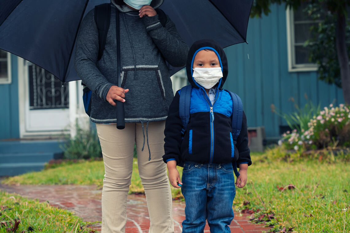 Little brother and older sister ready for school while wearing a face mask and backpacks during virus outbreak.
