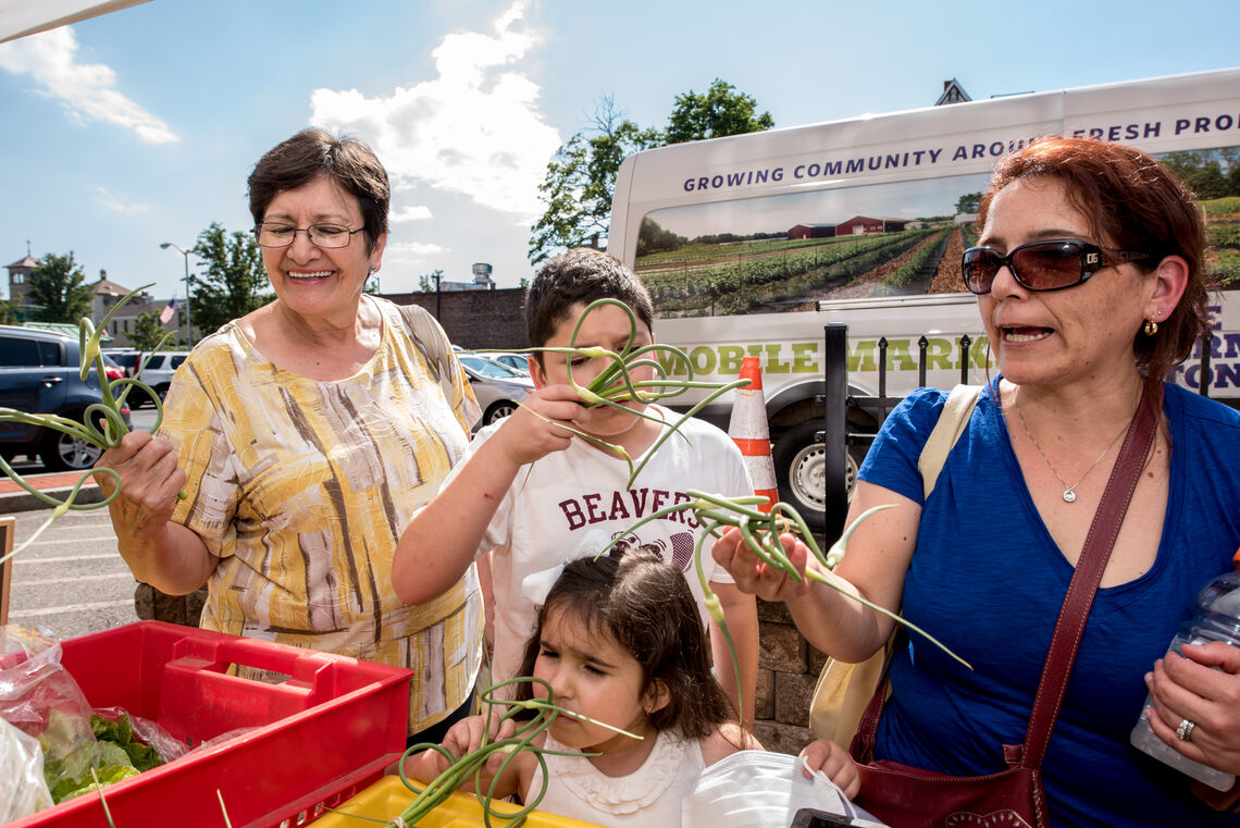 A two generation Latino family shops for fresh, local produce at Stonehill Mobile Market, curiously smells fresh garlic scapes.