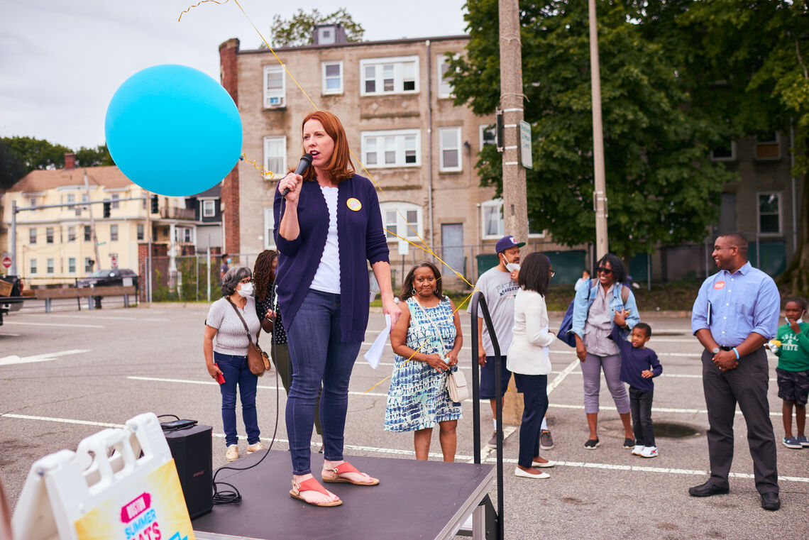 Erin Mcaleer stands on a platform, speaks to a crowd at opening day of Mattapan Food & Fitness Coalition farmers market
