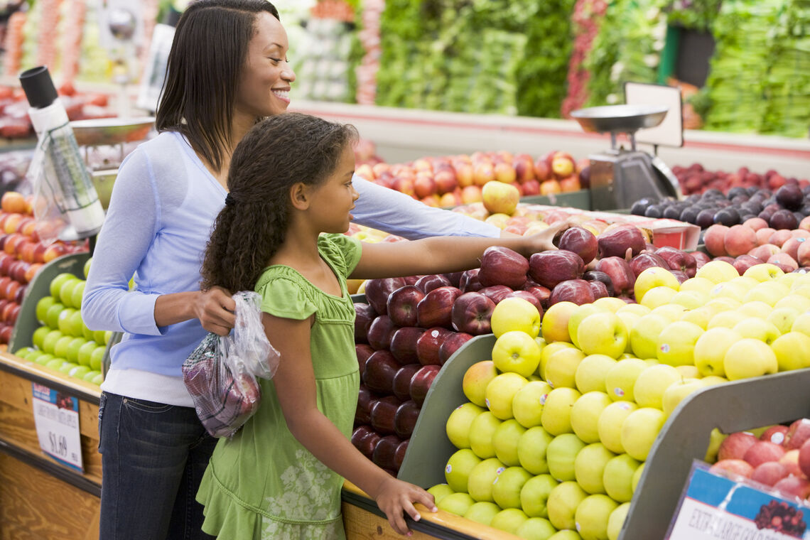 mom and daughter shopping for produce in grocery store