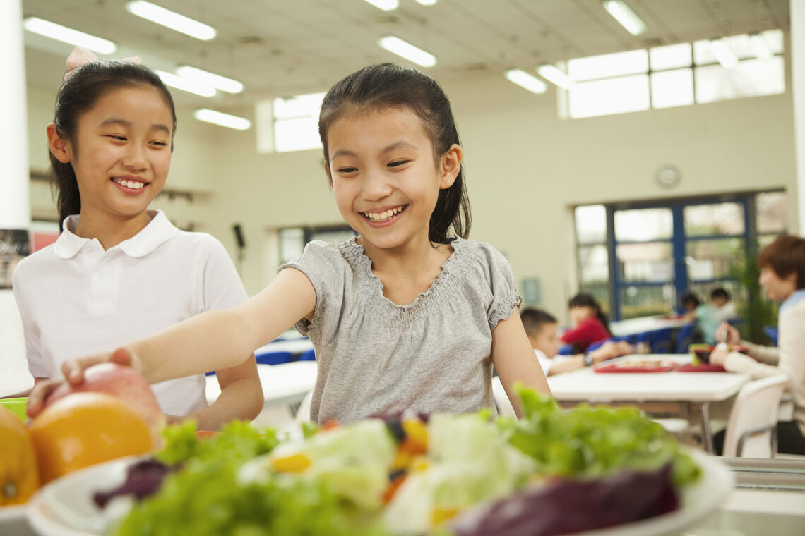 girl reaching for salad during school lunch