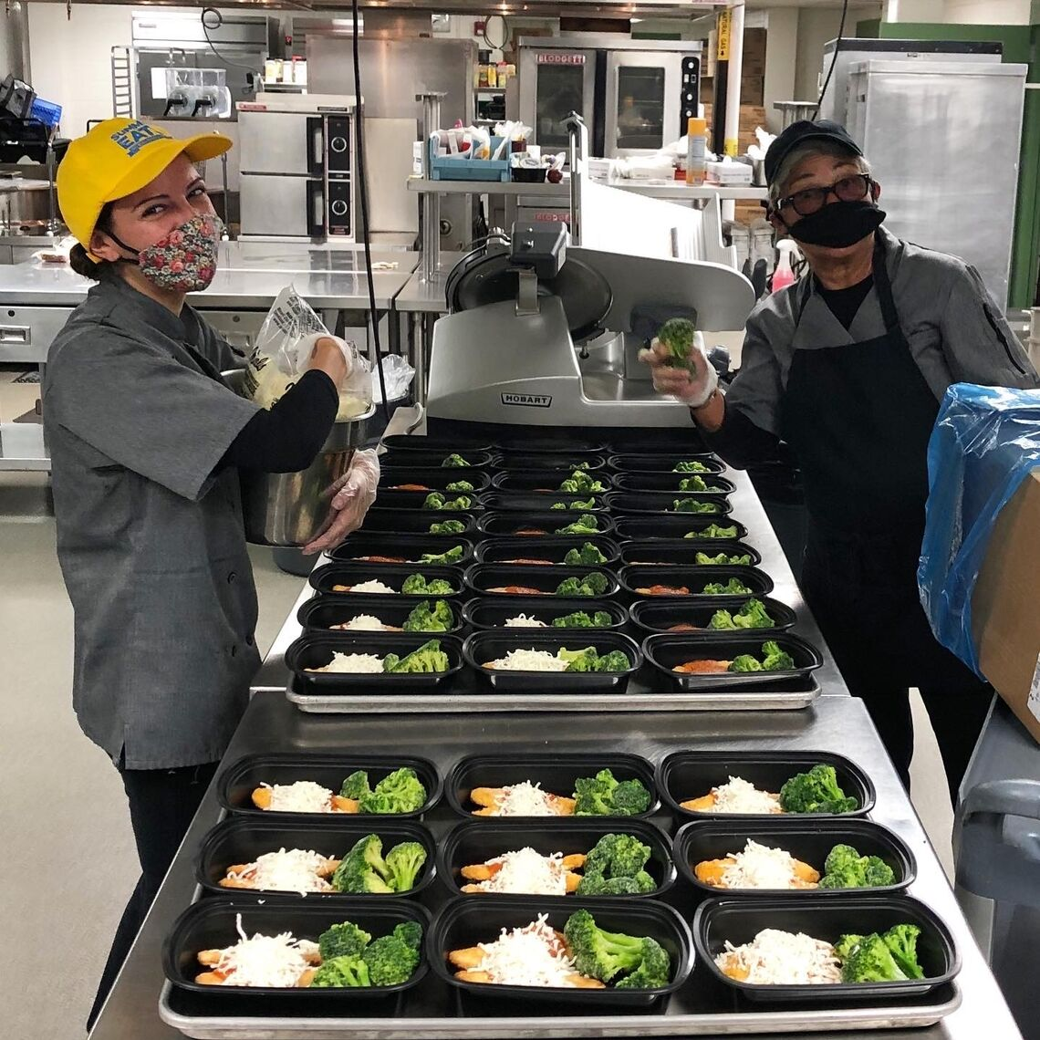 Two school nutrition professionals working hard to prepare school meals for kids through pandemic